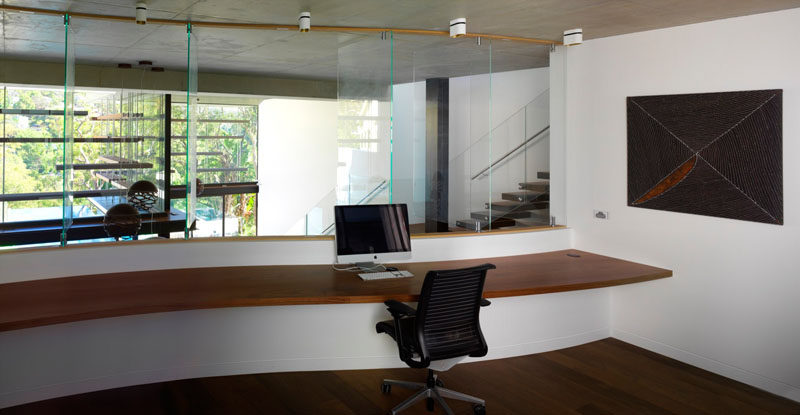 This large home office has a built-in floating wood desk that overlooks the main living room below.