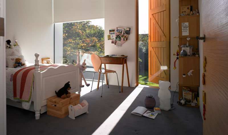In this kids bedroom, white roll down blinds that match the walls are used for privacy.