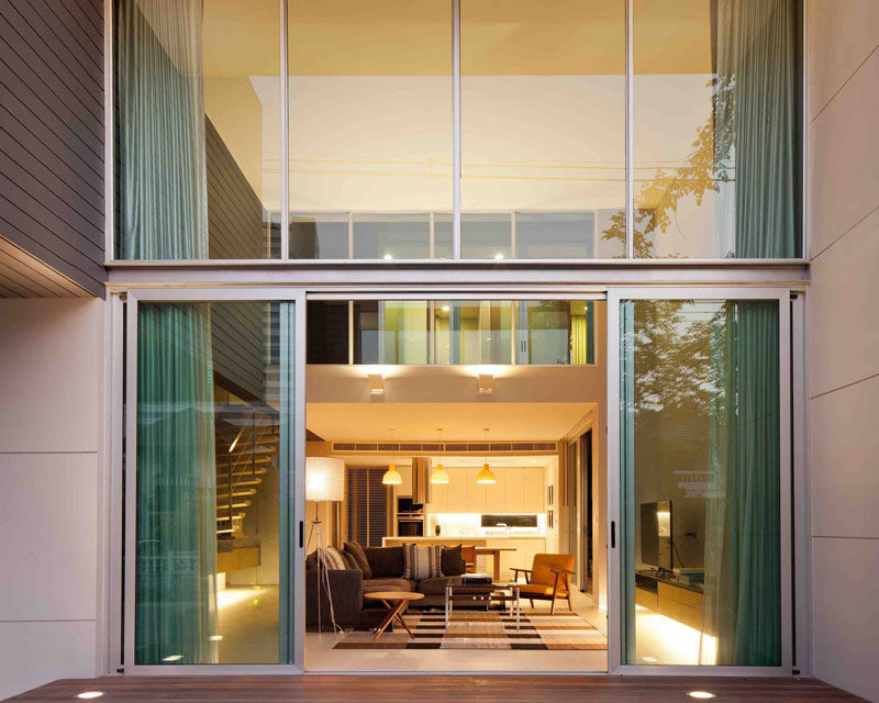 Large windows and sliding glass doors fill the double-height interior of this modern house with plenty of natural light.
