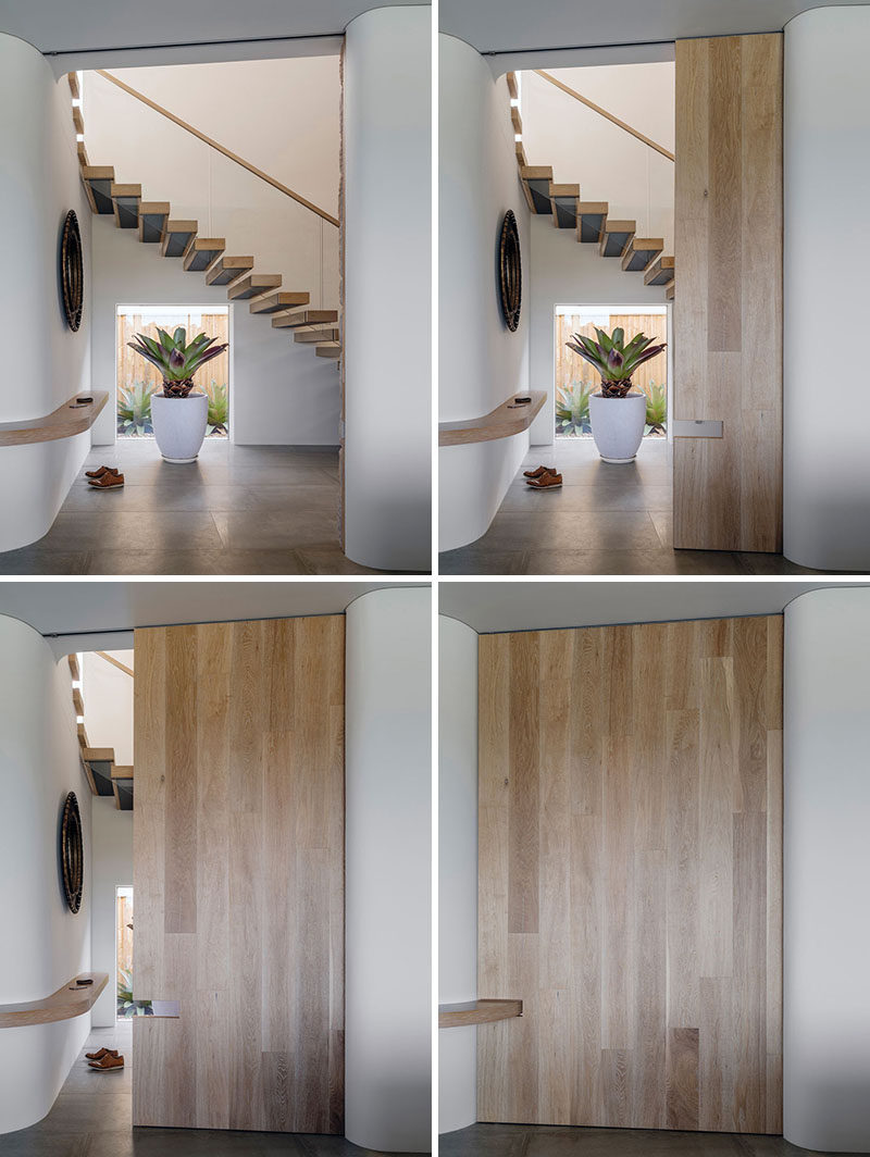 In this modern house, a large sliding wood door can be closed to hide the stairs and entryway from the main living space, while a continuous shelf between the two spaces is the ideal spot for dropping your keys and phone when you walk inside.