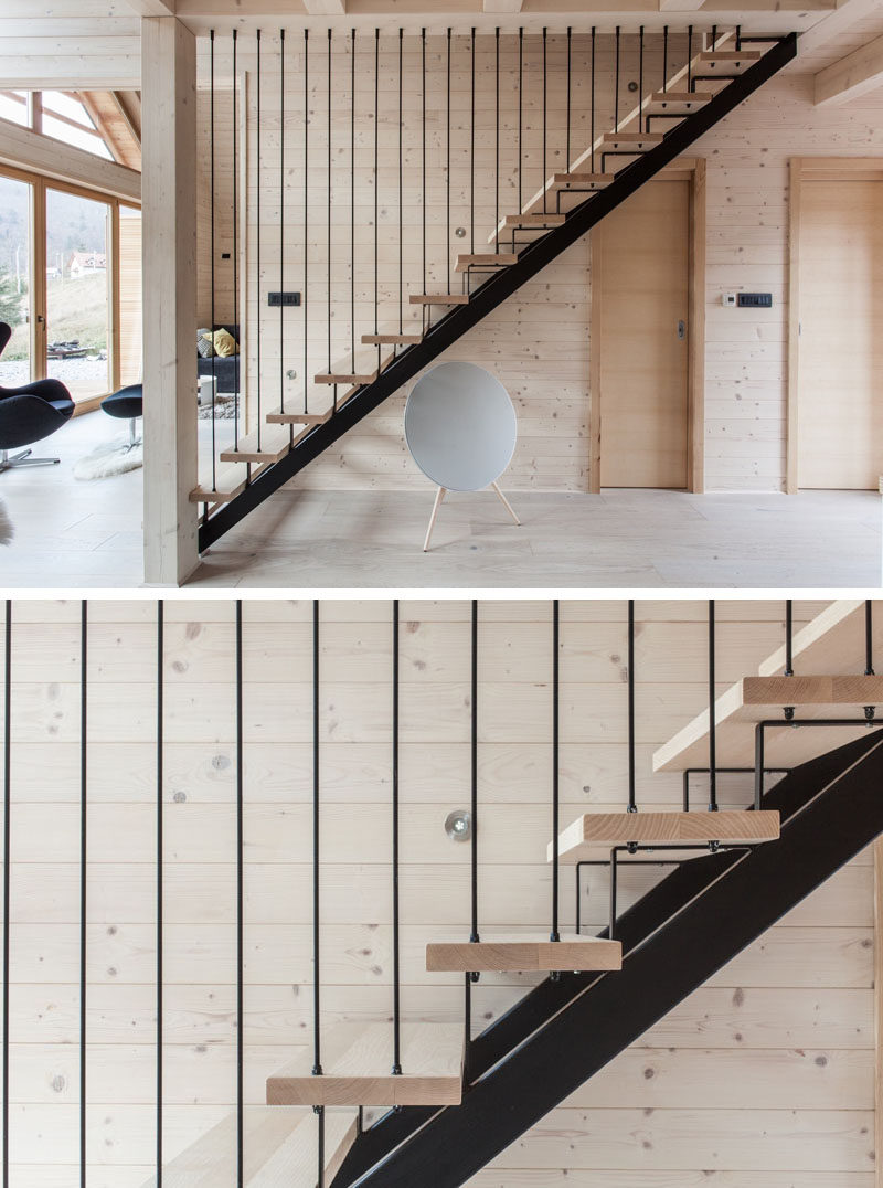 Black steel and light wood stairs lead to the upper floor of this modern house.