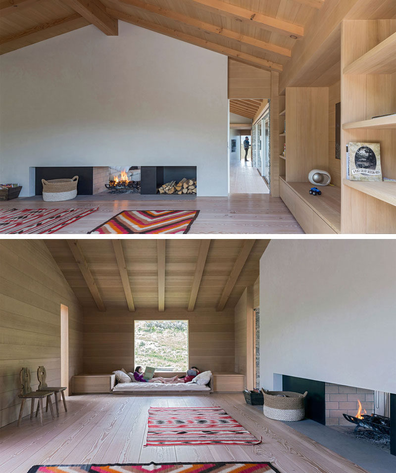 This modern house has a secondary living space, with a double-sided fireplace, built-in book shelves and a built-in day bed under the window.