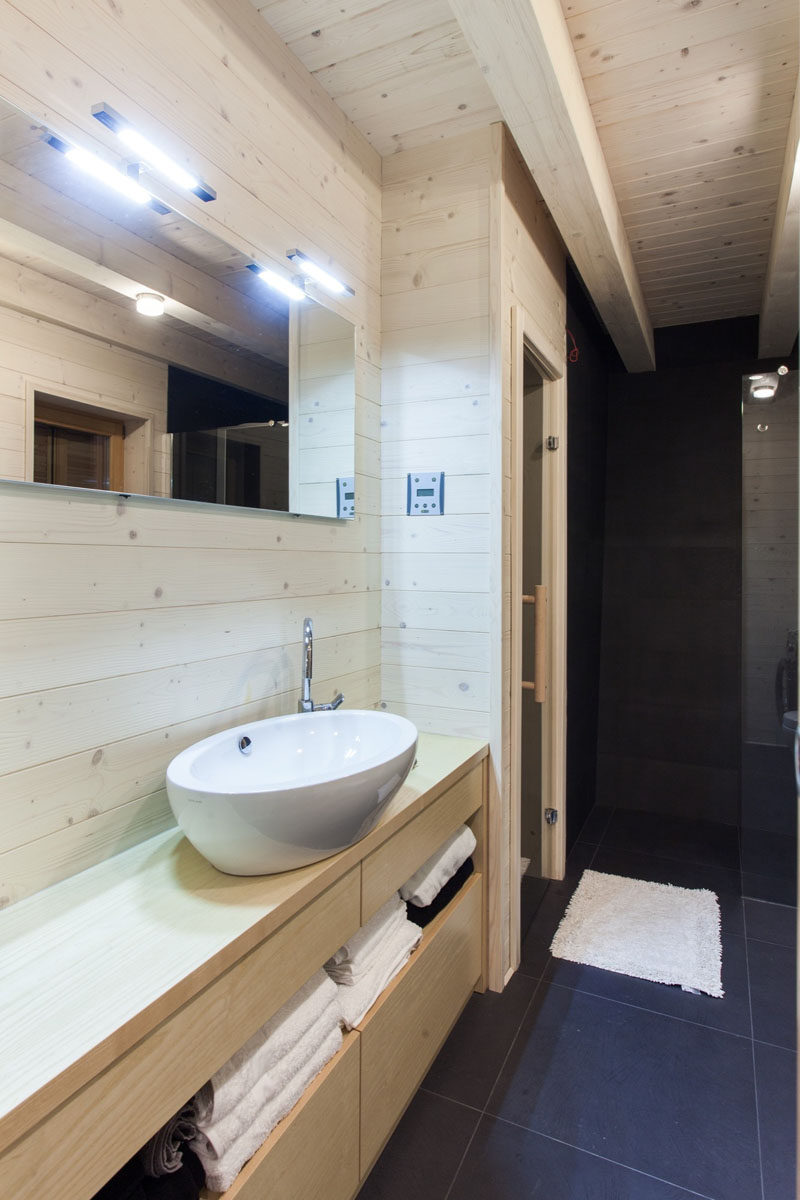 This light wood bathroom has a black shower and flooring for a rustic modern look.