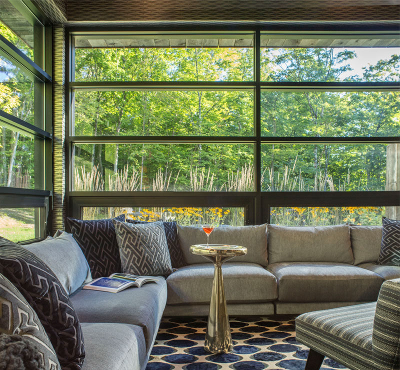 This contemporary living room has a corner sofa that wraps around the space, and black framed windows let plenty of natural light into the room and provide views of the landscape outside.