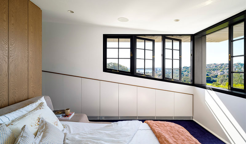 This master bedroom features black framed windows that can be opened, while deep eaves provide protection from the sun.