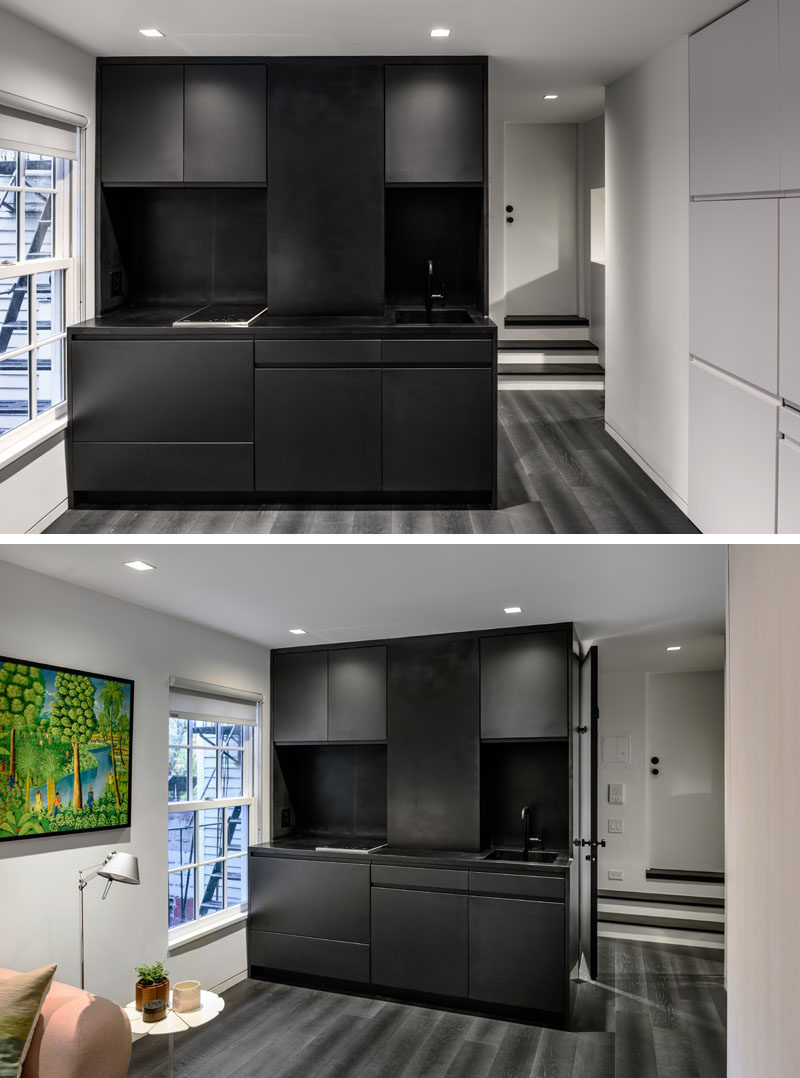 The black kitchen is the only dark space in this micro apartment and it has a compact design, with a small sink and a tiny cooktop. The designers have maximized the amount of cabinet space by having them go all the way to the ceiling.