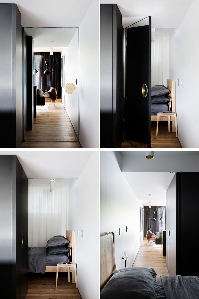 This modern apartment features a mirrored door with an over-sized door handle that hides a bedroom.