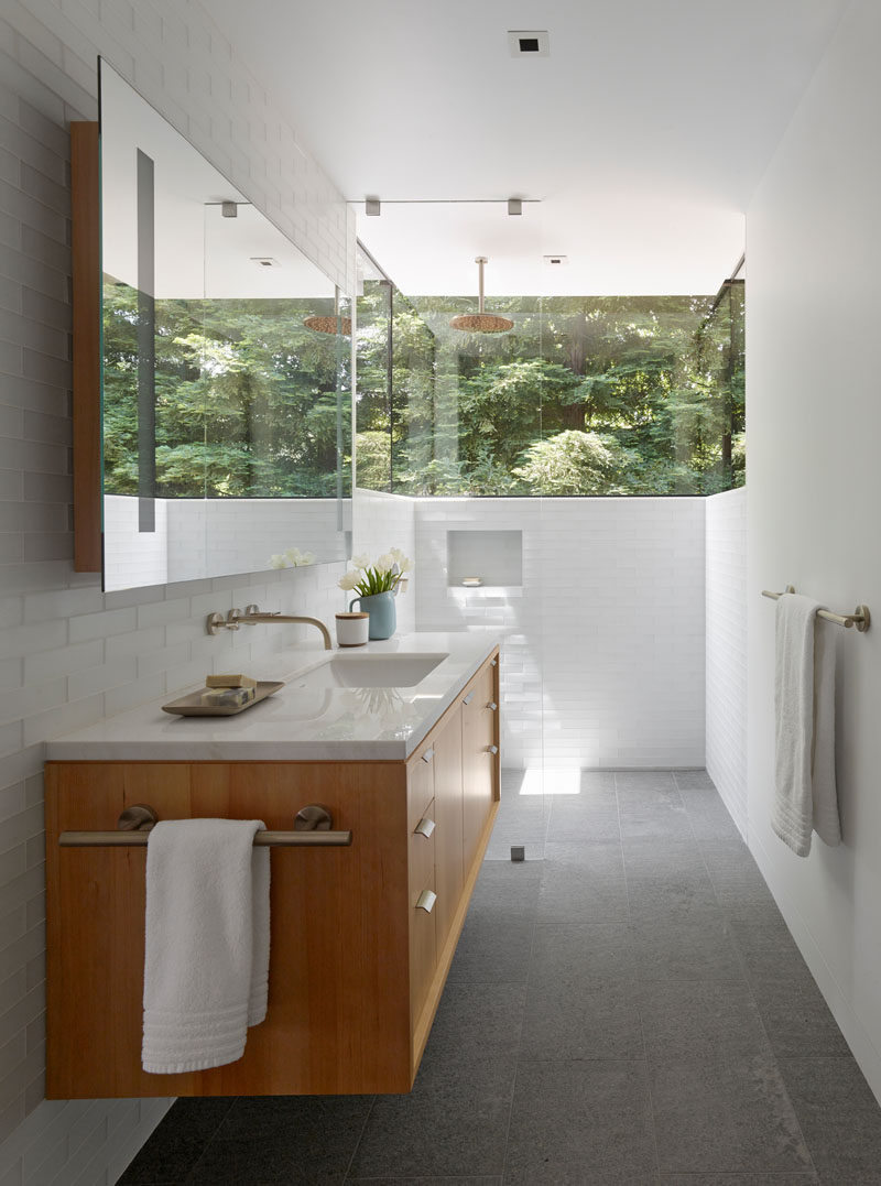This modern and updated bathroom has white walls and white tiles, and a wrap-around window makes you feel like you are showering in nature. A light wood vanity with white countertop, light grey tile flooring and a large mirror help to keep the bathroom bright.