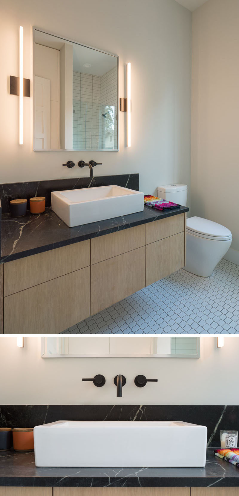 This modern bathroom features a floating vanity with a black countertop and sconces that flank the mirror.