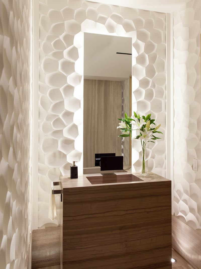In this small and modern bathroom, sculptural white panels surround a backlit mirror.