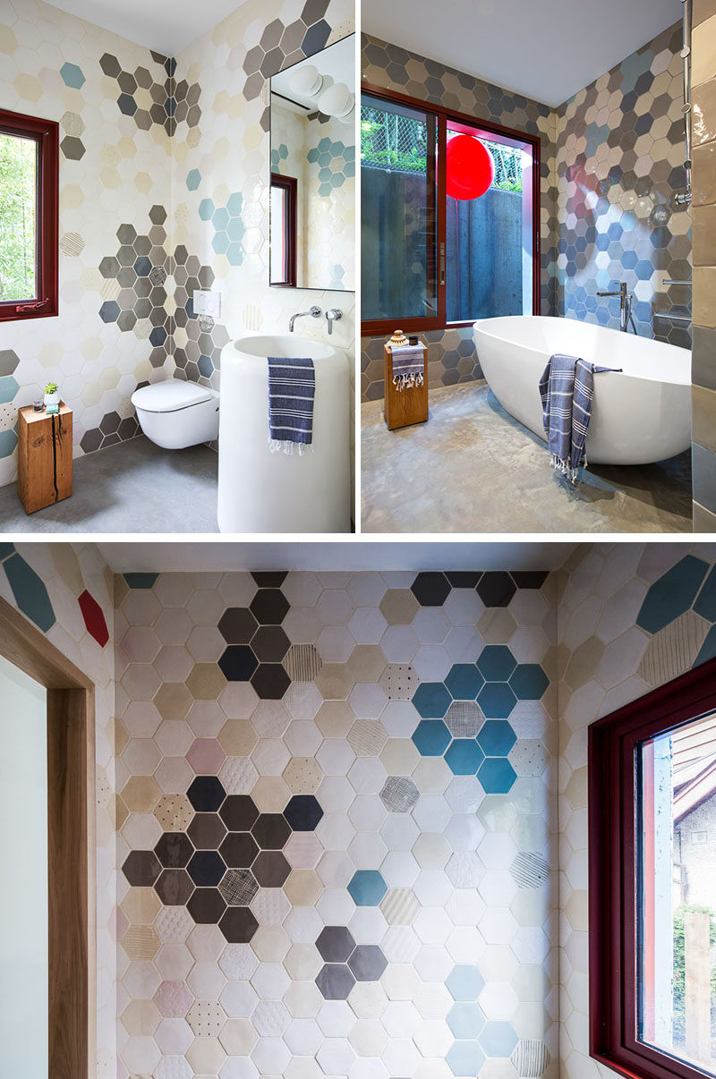 In this modern bathroom, hexagon tiles in a variety of colors ranging from light to dark, cover the walls from the floor right up to the ceiling.