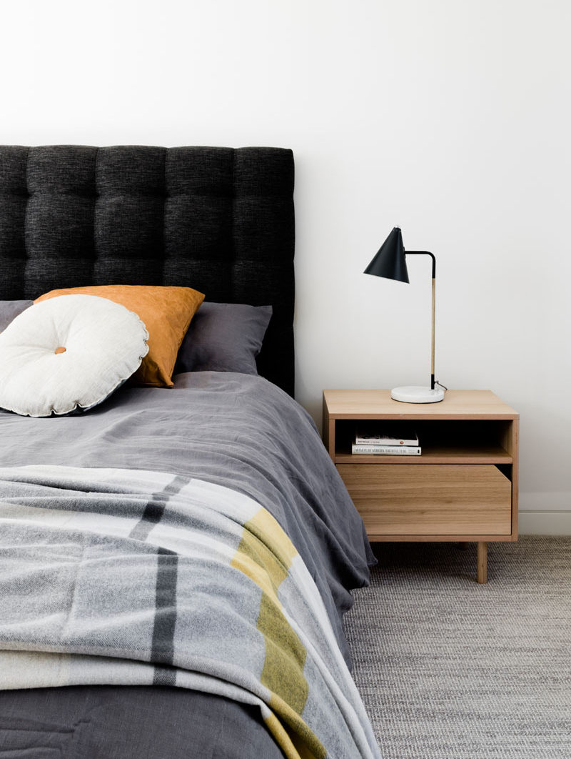 In this modern bedroom, the walls and flooring have been kept light. The dark grey upholstered headboard and the black lamp create contrast, and the light wood nightstand ties in with the other wood elements in the home.
