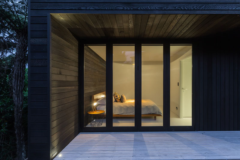 The black wood exterior siding on this small modern house continues through to act as a feature wall in this bedroom.