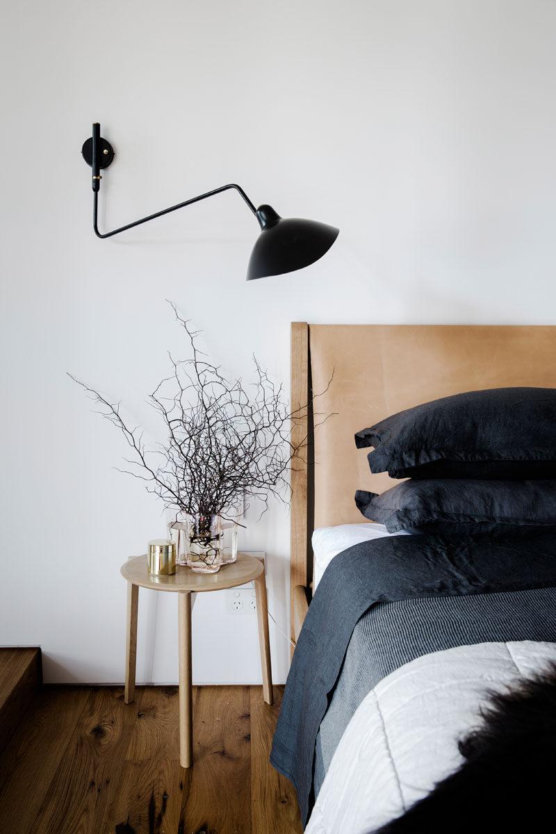 This modern bedroom features a black wall lamp, and a wood bed frame with a leather headboard.