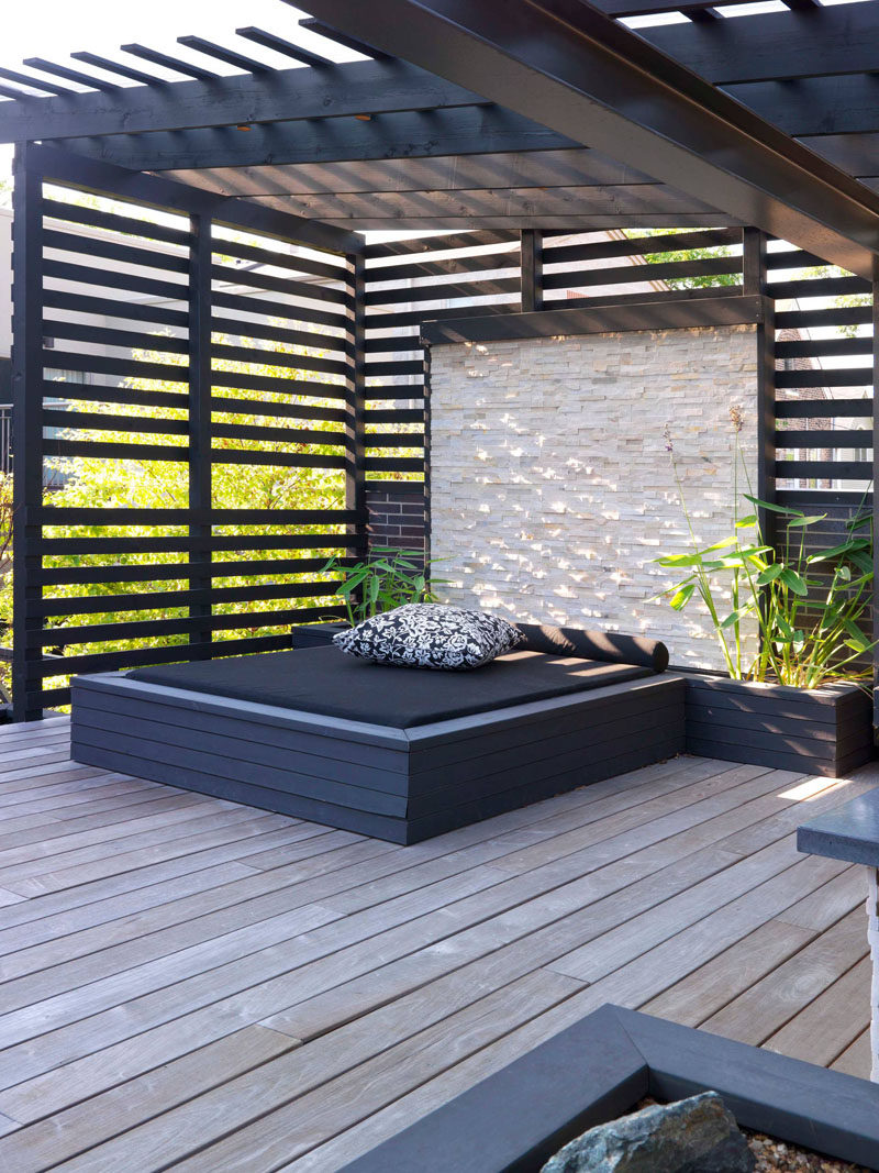 This built-in outdoor day bed with a stone wall and planters sits underneath a pergola that provides shade.