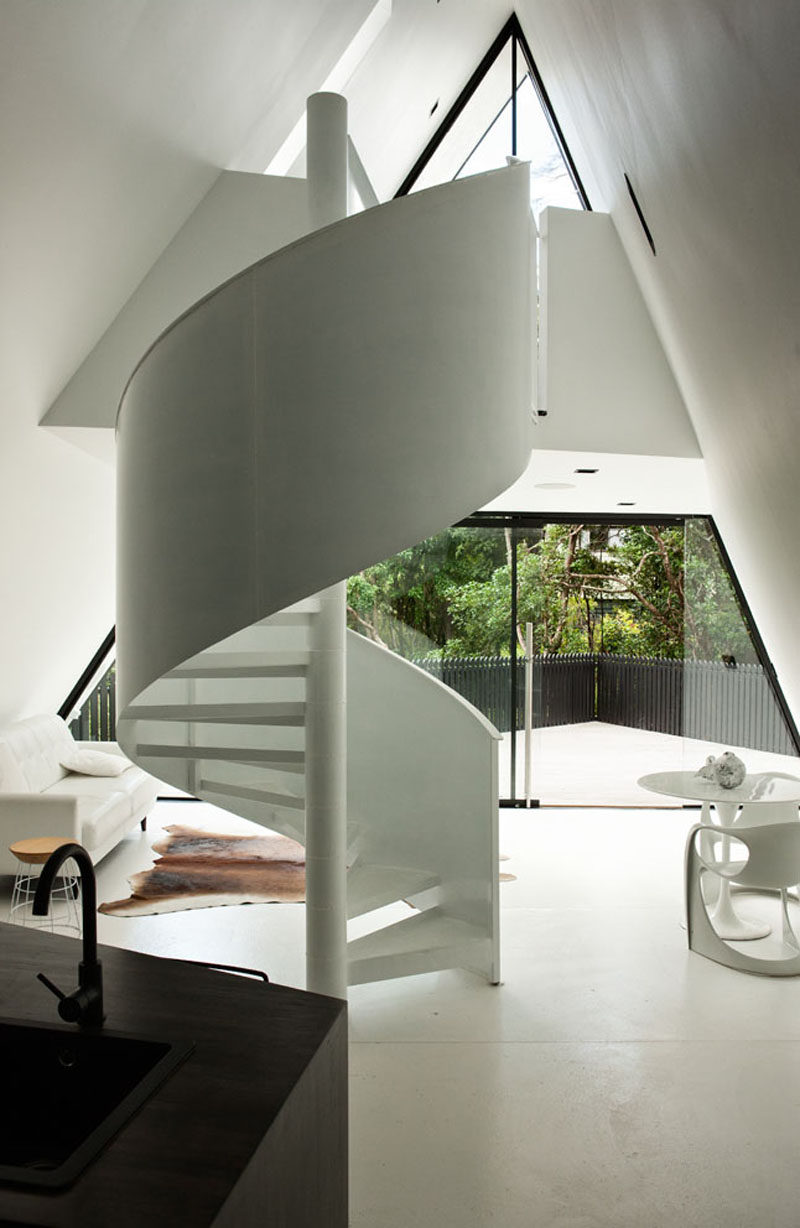 This small and modern cabin has a white spiral staircase that leads to the bedroom.
