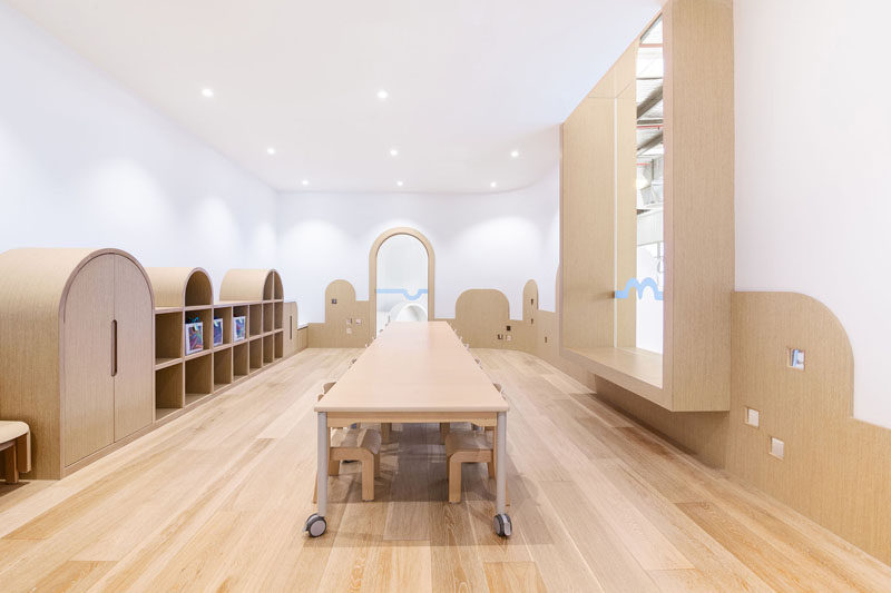 In this modern playroom, there's a single long table on wheels for groups of children, and curved wood details along the walls spark the children's imagination and allow them to believe they could be buildings, mountains, or anything else their minds think of.