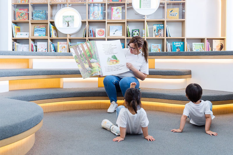 In this modern library, children can sit and read by themselves, or with an adult. Tiered seating with upholstered cushions and hidden lighting creates an ideal space for storytelling.