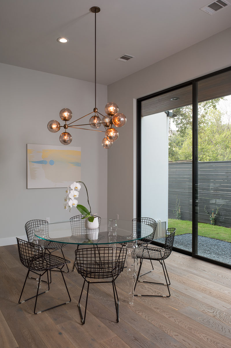 A sculptural glass pendant light anchors the round glass dining table in the open floor plan. Large windows provide views of the garden outside.