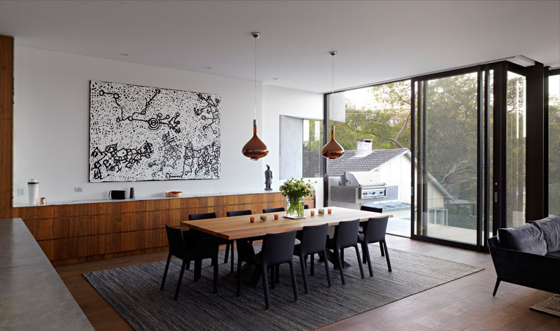 In this modern house, the dining room is located just off the kitchen, and the wood kitchen cabinets continue through to become a long sideboard.