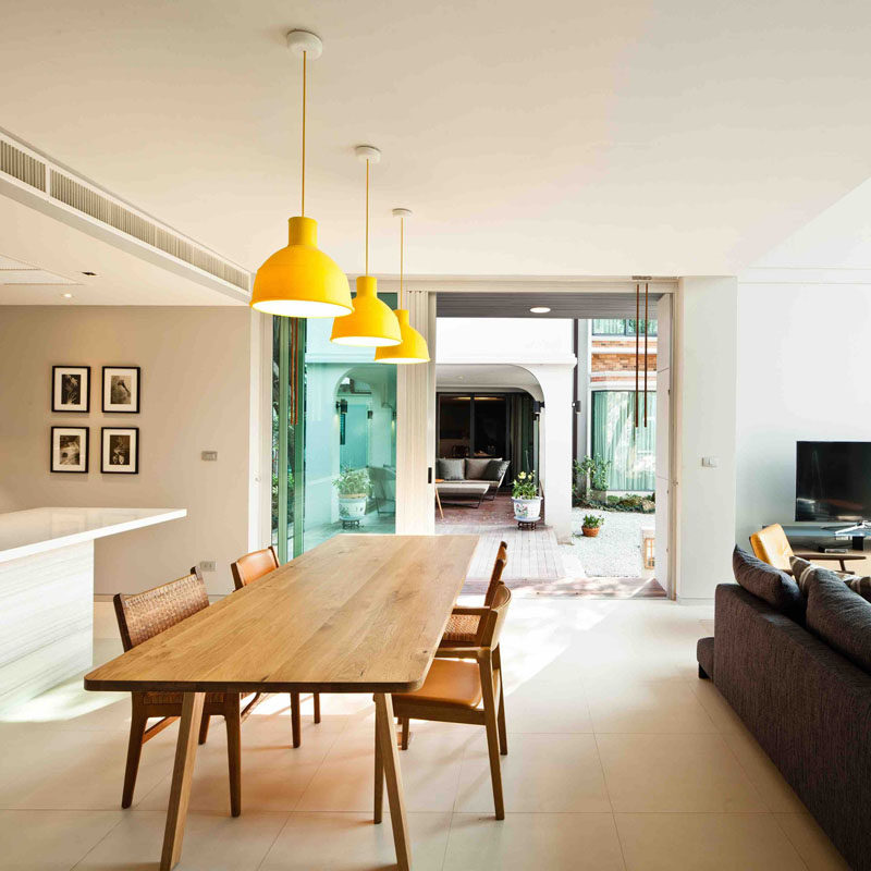 This modern dining room is made up of a large wood dining table with three yellow pendant lights adding a pop of colour to the space.