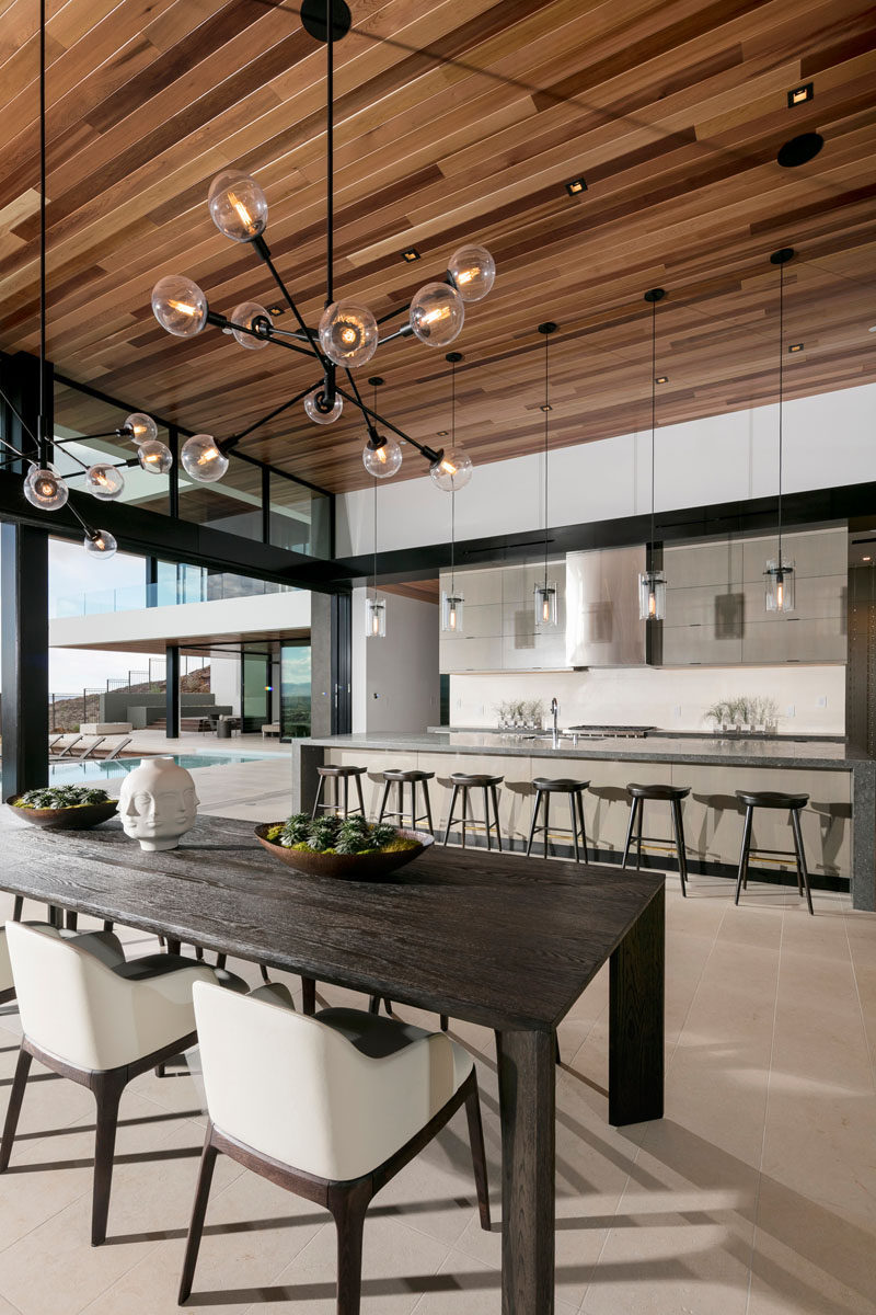 This modern dining room, with a large dark wood table, is anchored in place by two sculptural pendant lights.