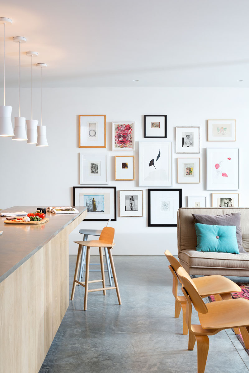 Between the living room and the kitchen in this modern house, is a wall decorated with a gallery of favorite art pieces.