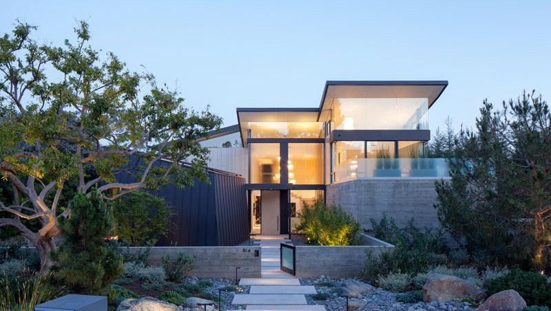 The Front Of This Modern House Has A Path Surrounded By Landscaping That Leads To