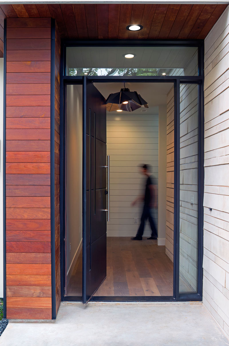 Welcoming you to this modern house is a large matte black pivoting front door, that's surrounded by windows, letting the natural light shine into the the home.