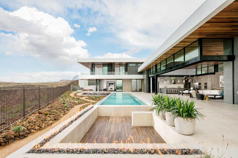 This modern house opens up to a large outdoor entertaining area and swimming pool, while a sunken area perfect for a few couches is surrounded by an outdoor fireplace.