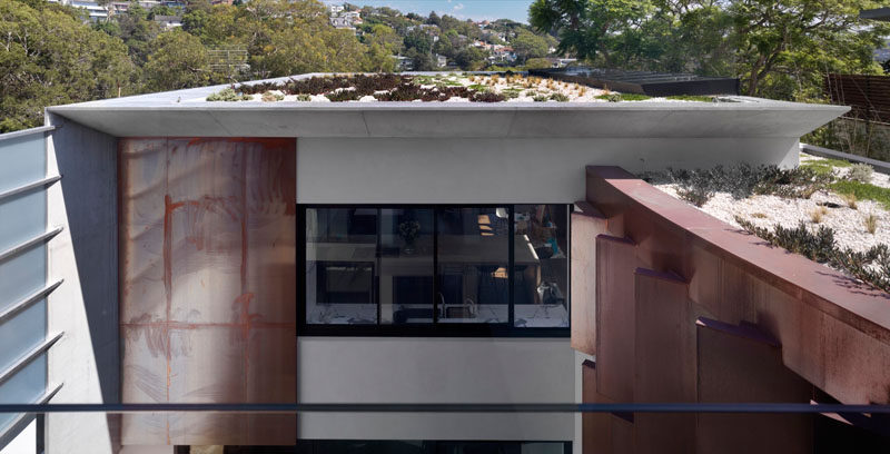 This modern house has a green roof to help with insulating the roof.