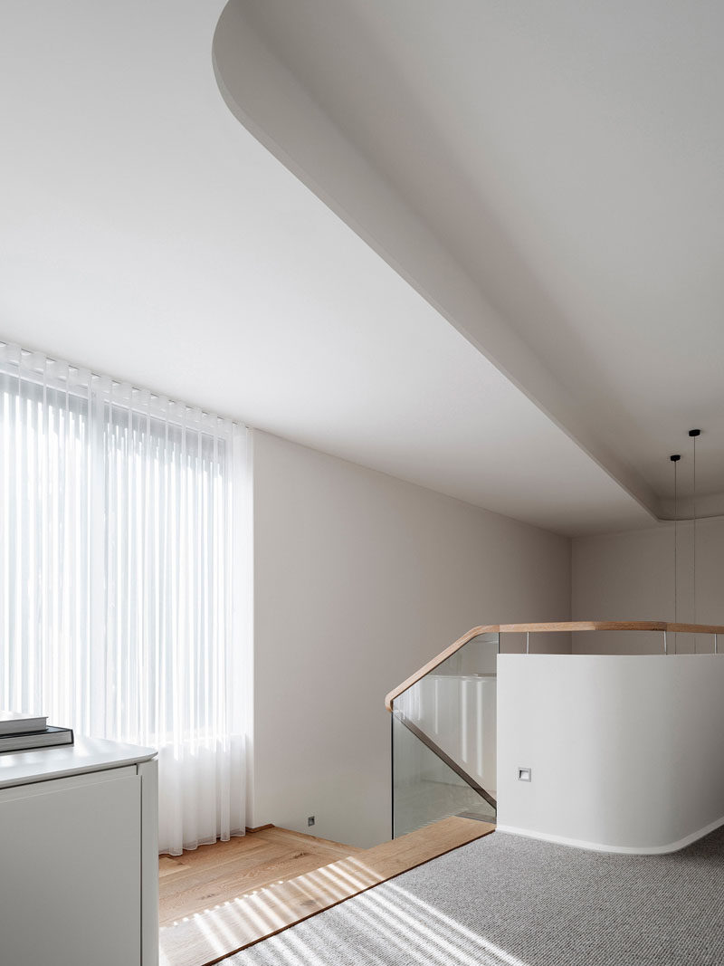 At the top of these modern stairs, there's curved walls and a curved ceiling bulkhead. One the floor the wood from the stairs transitions to a light grey carpet.