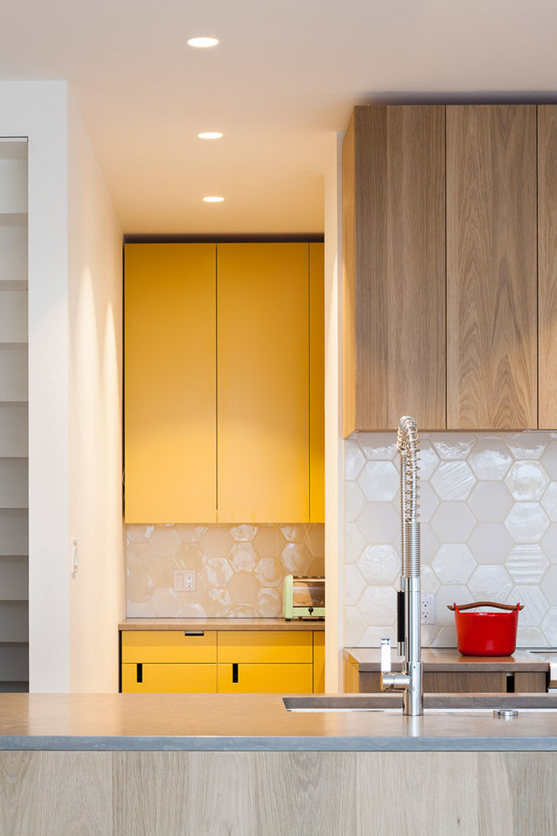 Behind this modern wood kitchen, is a hidden pantry room and secondary kitchen with yellow cabinets, that has the ovens and plenty of additional storage space.
