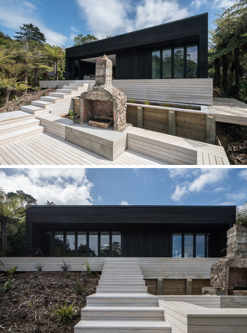 Simplicity and symmetry was key in the design of this modern holiday house, while dark cedar cladding covers the exterior, light wood stairs lead up to the home. Off to the side of the stairs is an outdoor entertaining area with a fireplace and built-in bench seating.