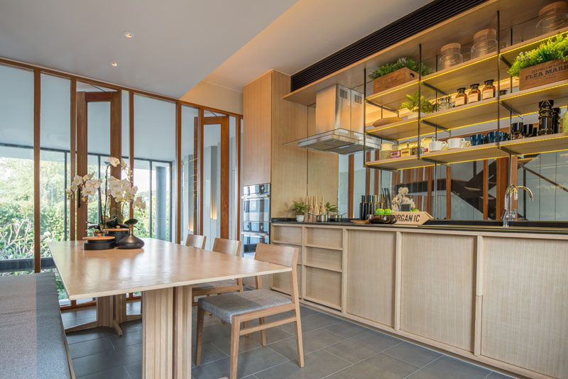 This modern kitchen has light wood cabinets, open shelving and a mirrored backsplash. The kitchen shares the room with the dining table. Floor-to-ceiling windows look over the living room below.