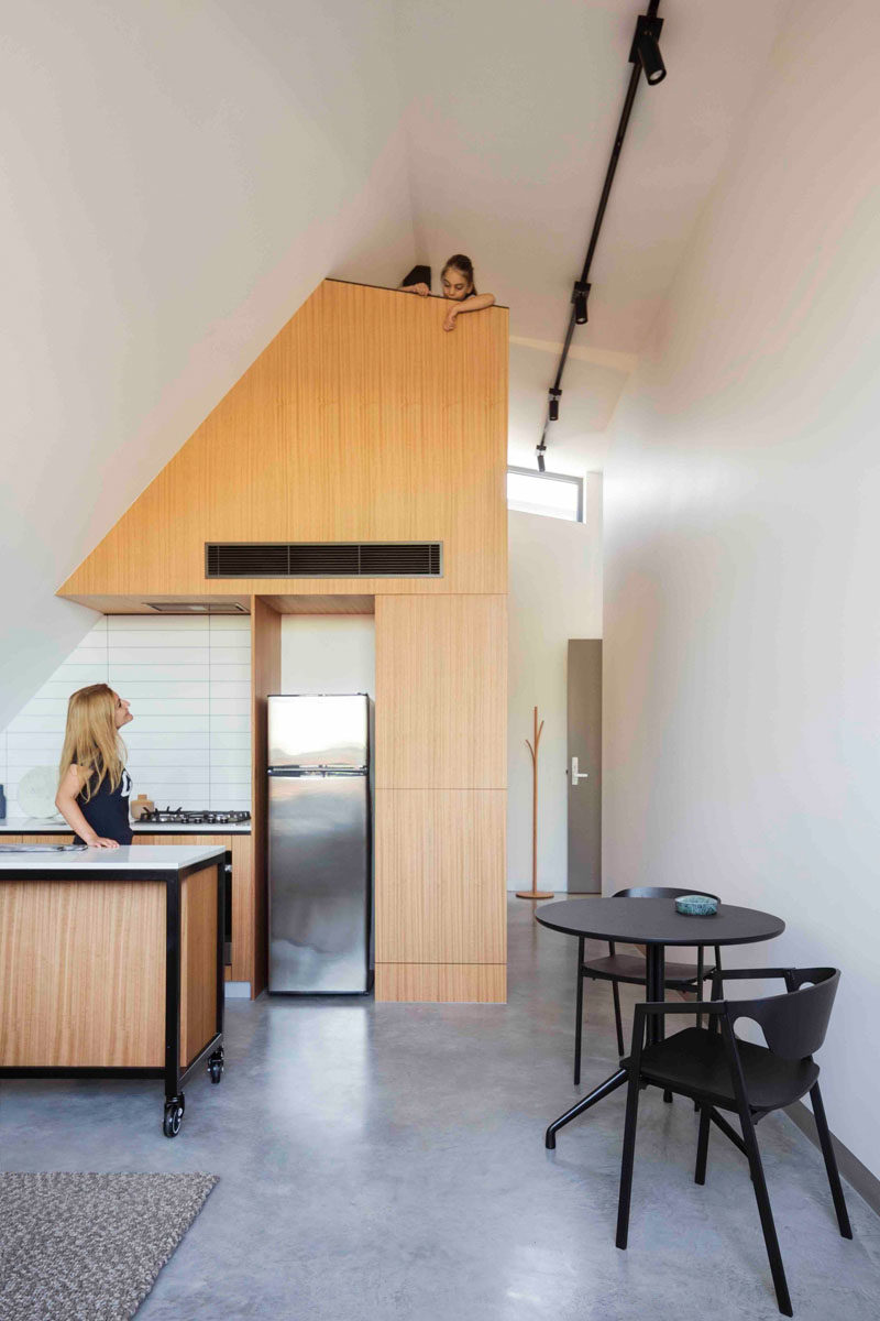 This modern apartment has a light wood and white tile kitchen, with a loft positioned above it.