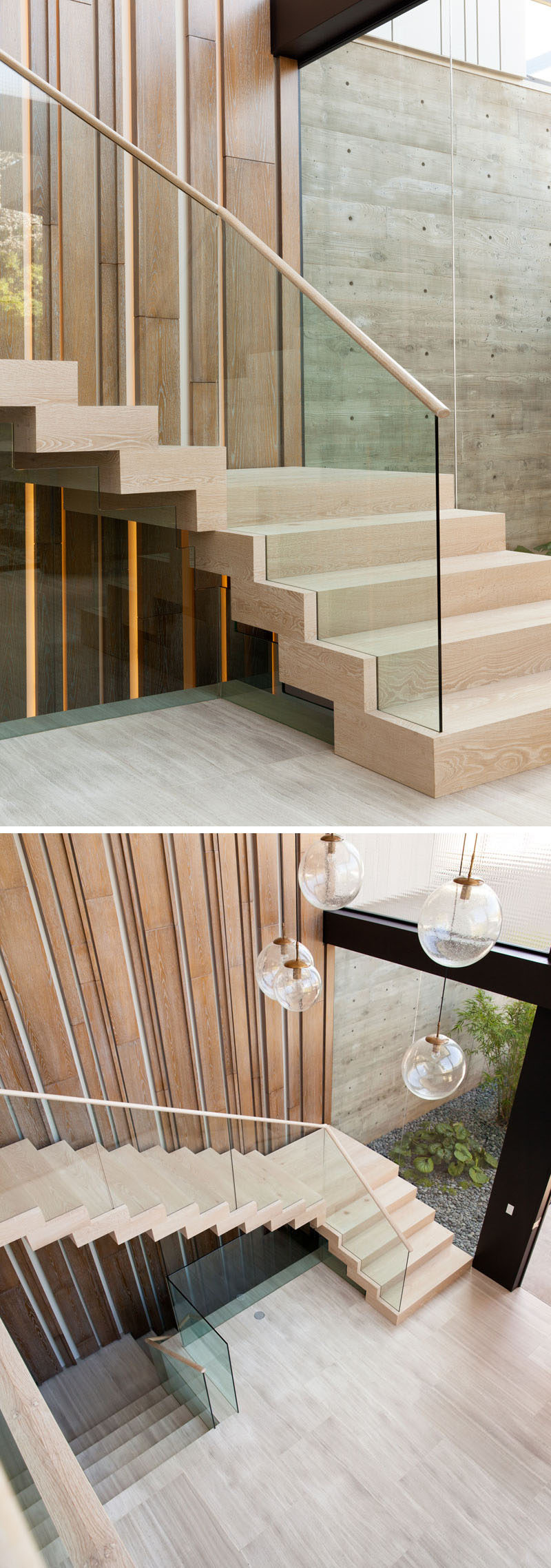 In this modern house, light wood stairs lead up to the second floor of the home, and a vertical wood accent wall with hidden lighting helps to emphasize the height of the foyer.