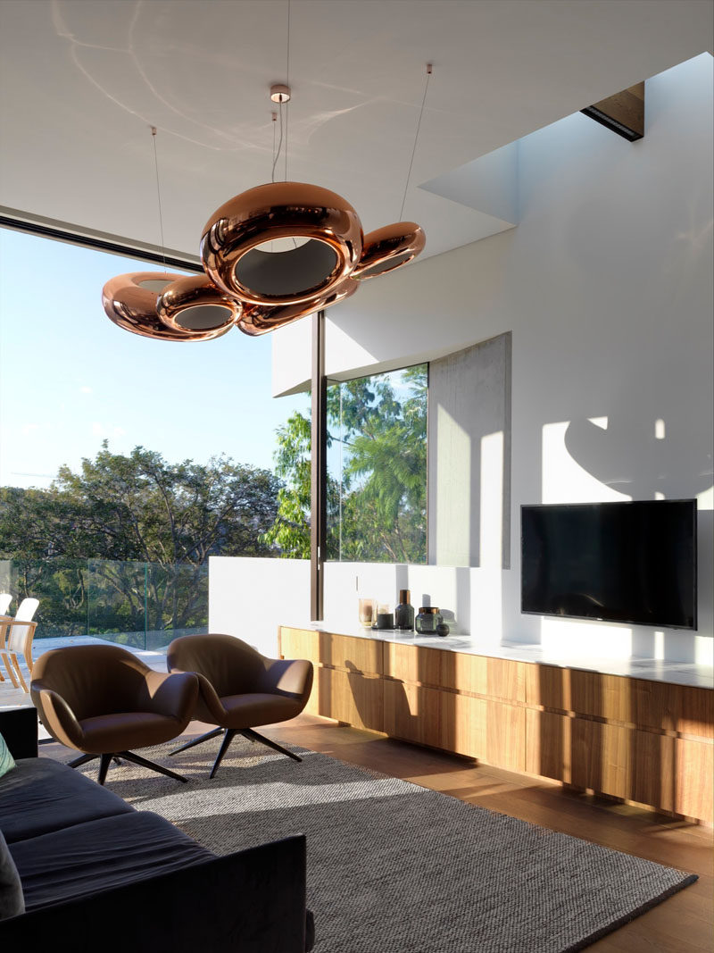 This small and modern living area features sculptural copper pendant lights and a light wood cabinet.