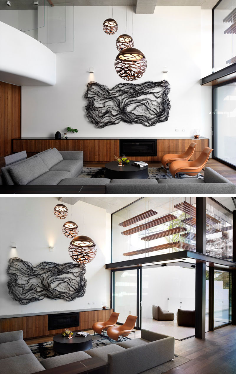 The lowest level of this modern house is home to a large living room that's located in a double height space. A large artwork hangs on the wall and sculptural pendant lights are positioned directly above the couch and arm chairs. Off the living room is an outdoor area.