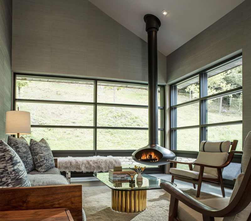 This modern living room has plenty of windows for natural light and views of the landscape outside, as well as a hanging fireplace for when it gets cold.