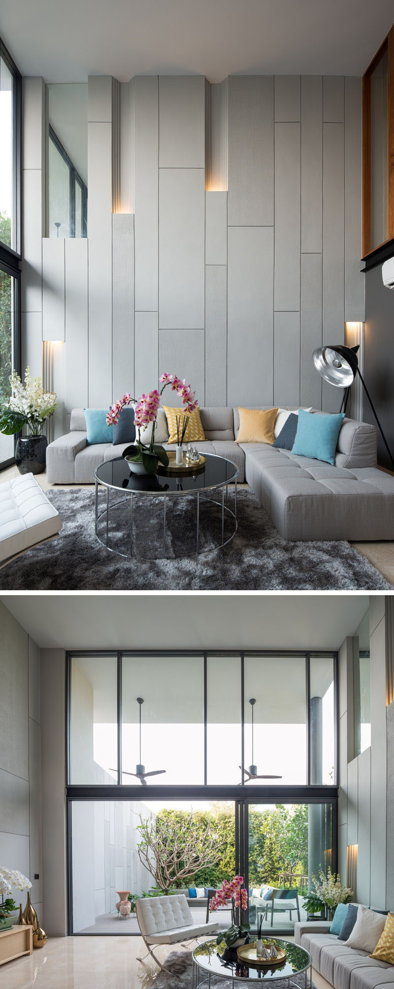 In this modern living room, the double-height space has large windows that look out onto the backyard. The wall behind the couch has built-in lighting to break up the solid wall, as well as helping to creating a unique atmosphere.
