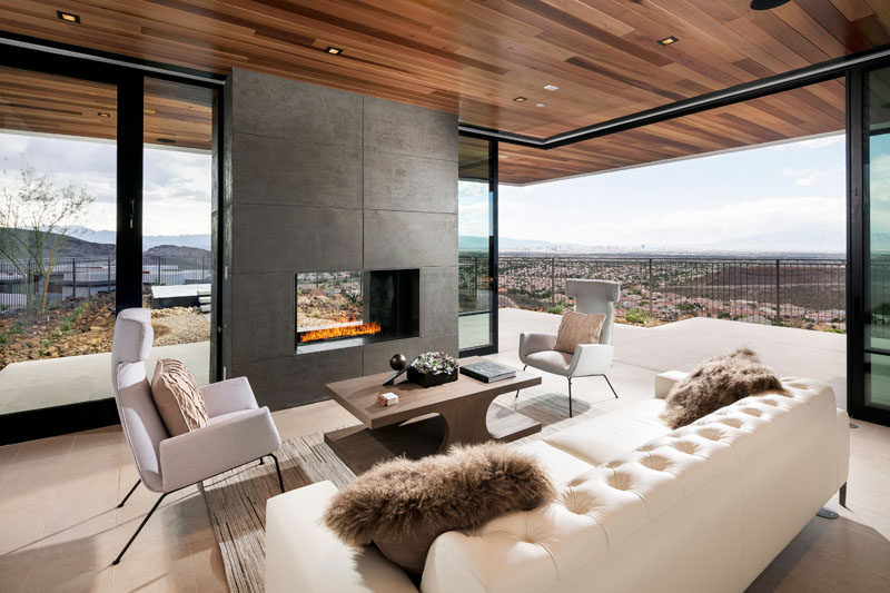 This modern living room with a wood ceiling is focused on the fireplace, and also has access to the outdoor patio area through sliding glass doors.