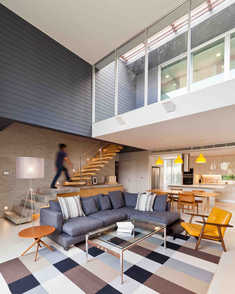 This modern house has a double-height ceiling in the living room, with the living room being anchored in the space by a large checkered rug.