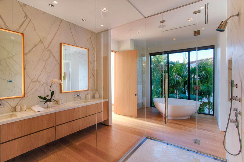 This modern master bath has a dual sink vanity, a shower with a floor-to-ceiling glass surround, and a white freestanding bathtub with views of the palm trees through the large windows.