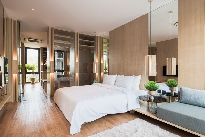 This modern master bedroom is full of light wood and mirrors. Small plants add a touch of nature to the room, and a built-in couch creates a place to relax and read a book.