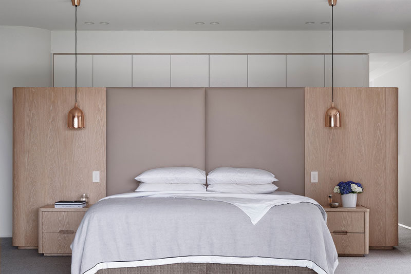 Symmetry was key in the design of this master bedroom with an upholstered headboard and hanging pendant lamps has beside lights.