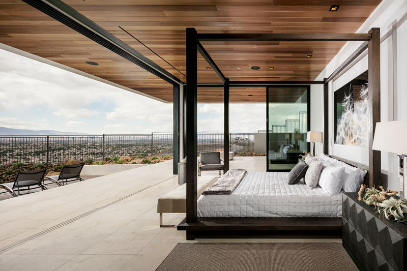 This modern master bedroom has a wood ceiling, uninterrupted views of the valley below and is completely open to the backyard and pool area.