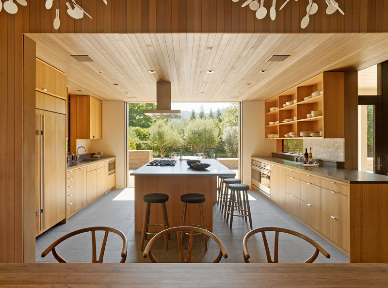 As part of this modern farmhouse renovation, the kitchen was opened up to the outdoors through large sliding pocket doors, and the original wood cabinets were replaced with modern cabinets and open shelving. Cedar siding was used to cover sections of the ceiling and walls throughout the renovated home.