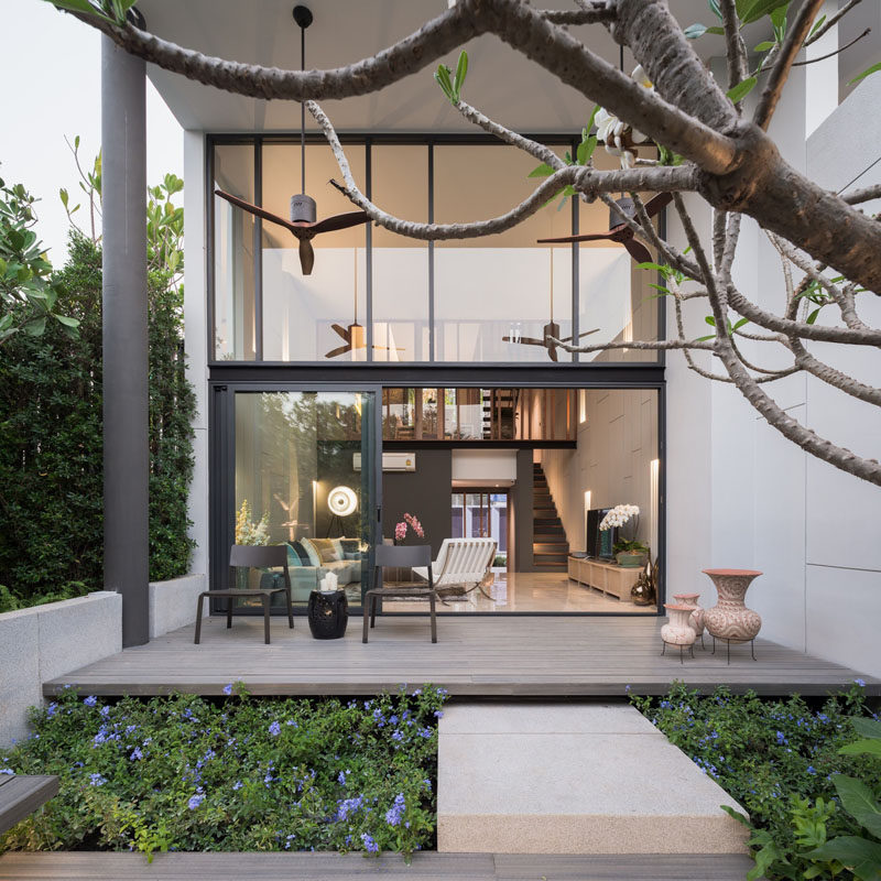 This modern house has a covered outdoor patio that looks out onto the backyard.