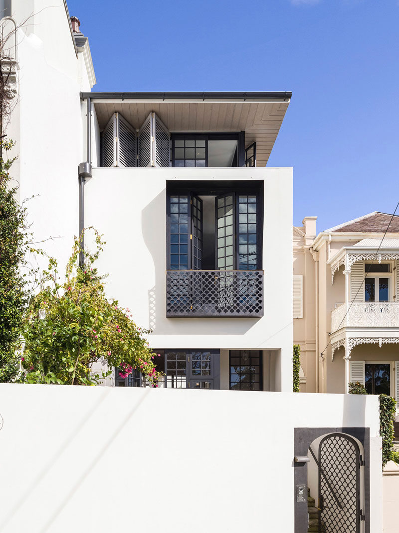 At the front of this renovated house, CNC cut steel plates in a fish scale pattern feature on the front gate and the Juliet balcony balustrade.